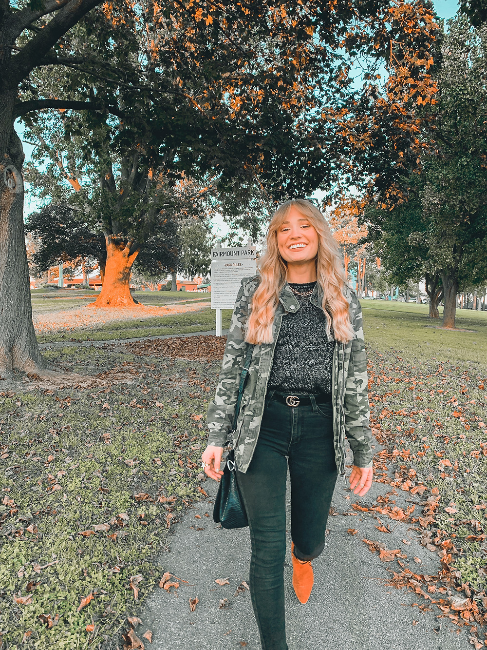 camouflage jacket, blonde hair, boots, black jeans, trees, park