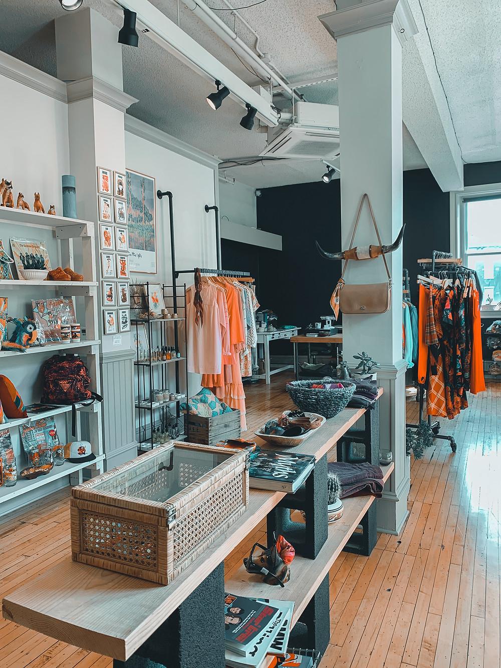store, shelves, clothing, wood floor, white walls, pillars, lights, vintage clothing