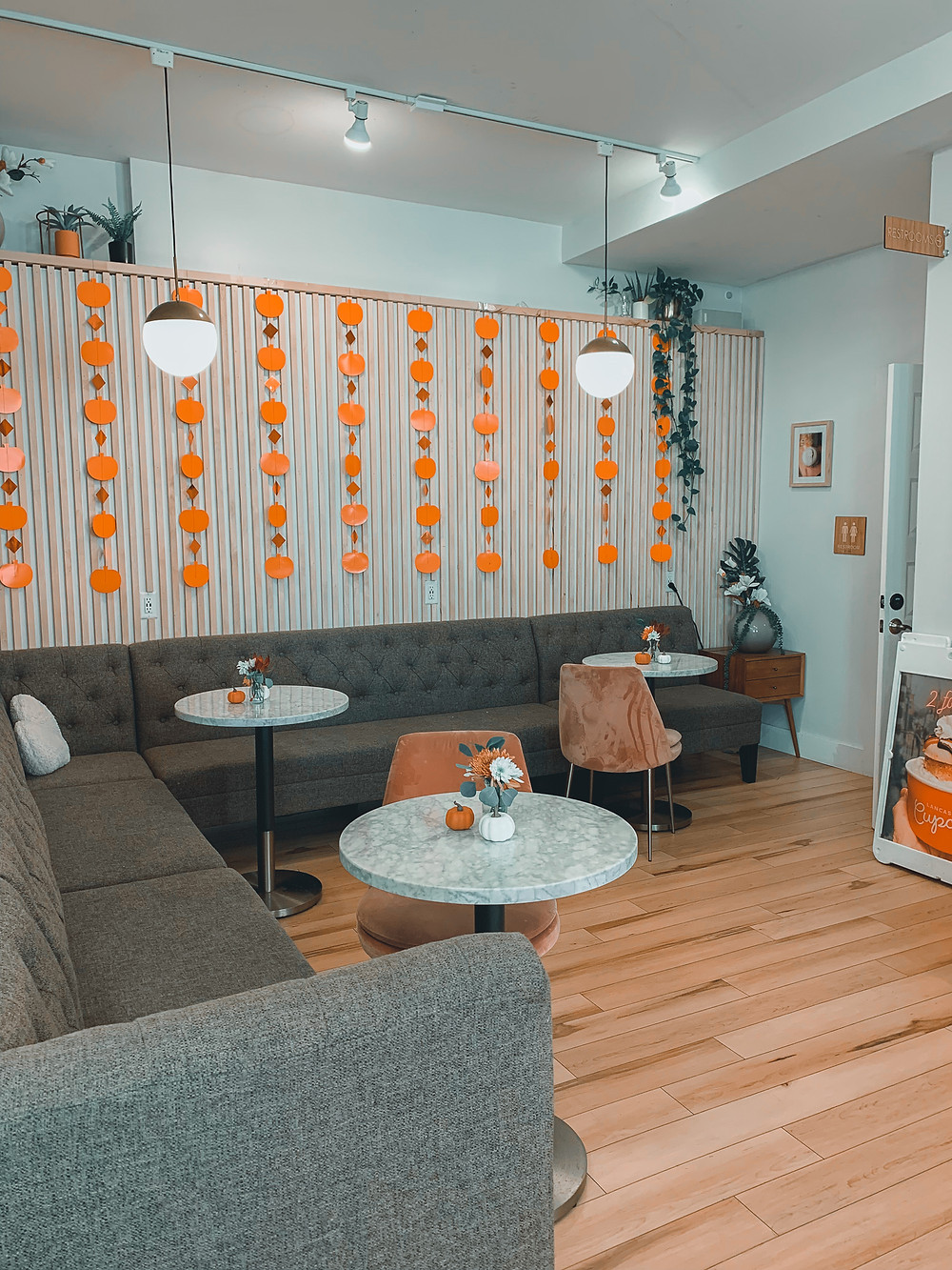 Lancaster Cupcake, wood floor, gray L shaped sectional couch, wall with wood detailing, small round granite tables, pink velvet chairs, orange pumpkin streamers
