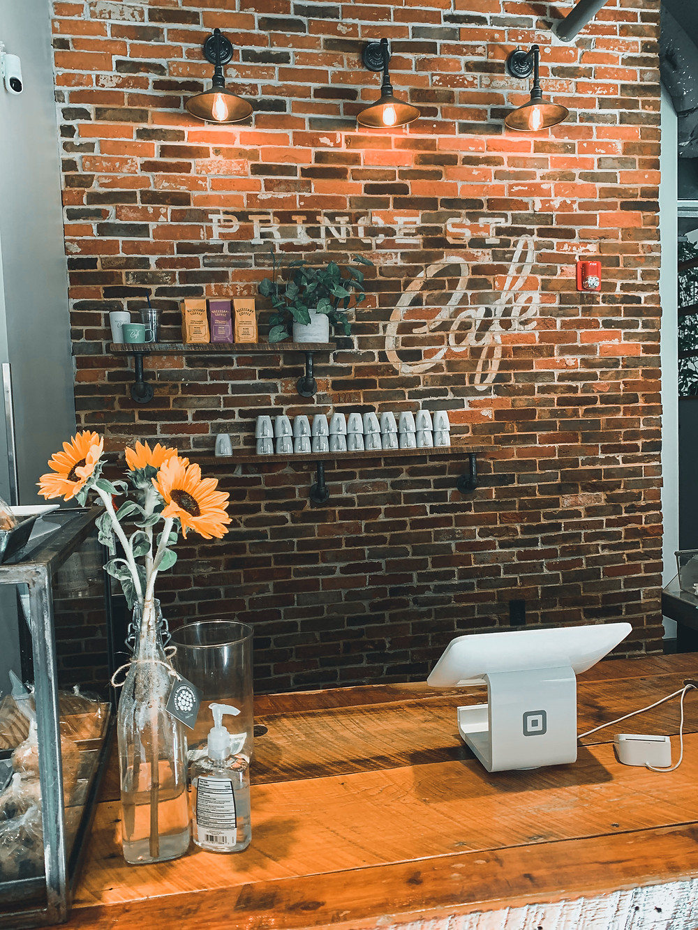 Prince Street Cafe, brick wall, cash register, sunflowers in vase, wood countertop