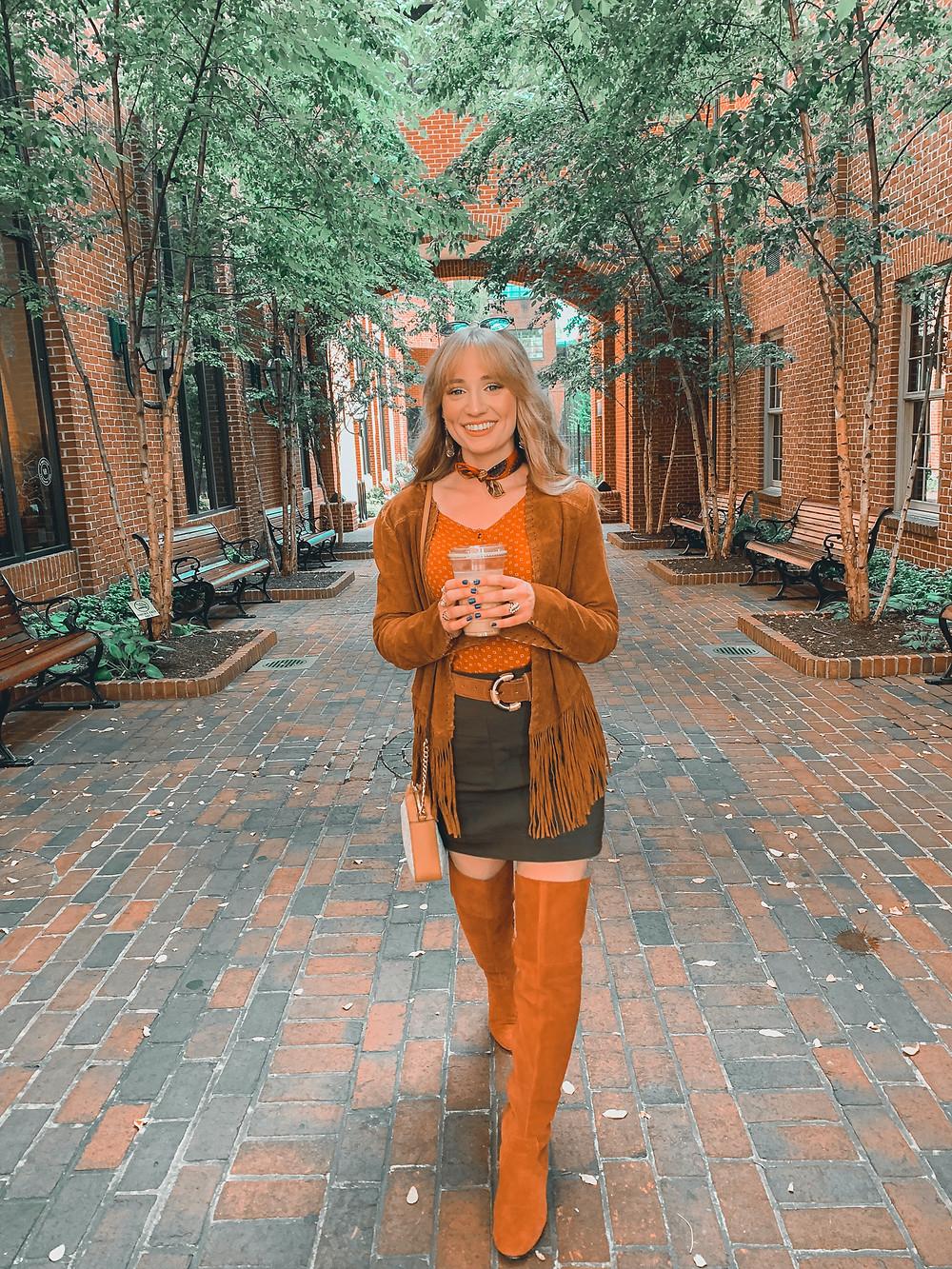 Blonde hair, scarf, orange shirt, brown suede fringe jacket, orange suede boots, dark green mini skirt, brown suede belt, brick building, brick walkway, green trees, street lights, benches