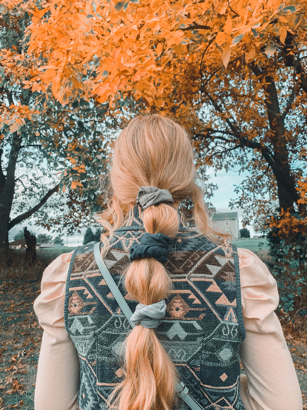 blonde hair, blonde ponytail, vest, aztec print vest, vintage clothes, thrifted clothes, April Heil, April M. Heil, fall leaves, orange leaves, jeans, Target boots