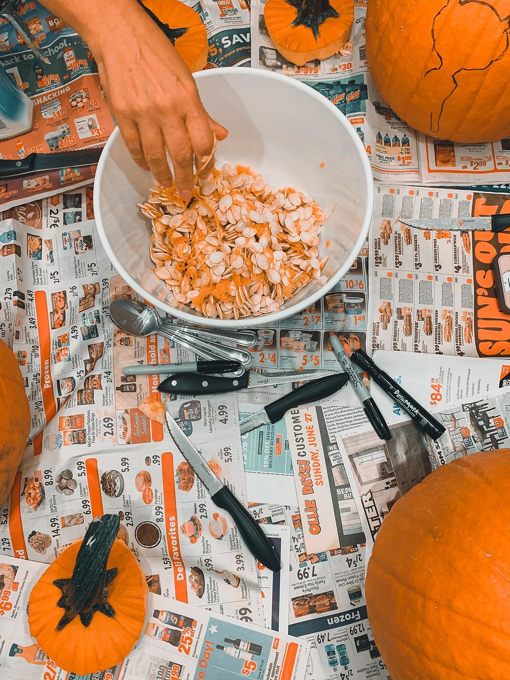 pumpkin carving newspaper orange pumpkin pumpkin seeds hand white bowl pumpkin stem knife knives newspaper markers sharpies