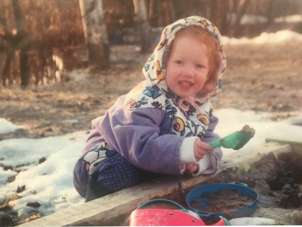 Paula as a kid playing in the sandbox in spring