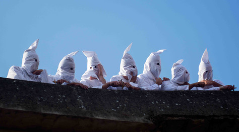 """""""Battenti"""" and """"disciplinanti"""" wear a white wax and a hood to hide their identifies."""