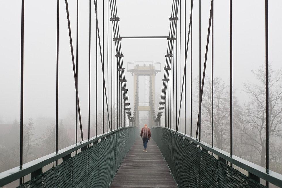 Une personne marche sur une passerelle pour se rendre de l'autre côté