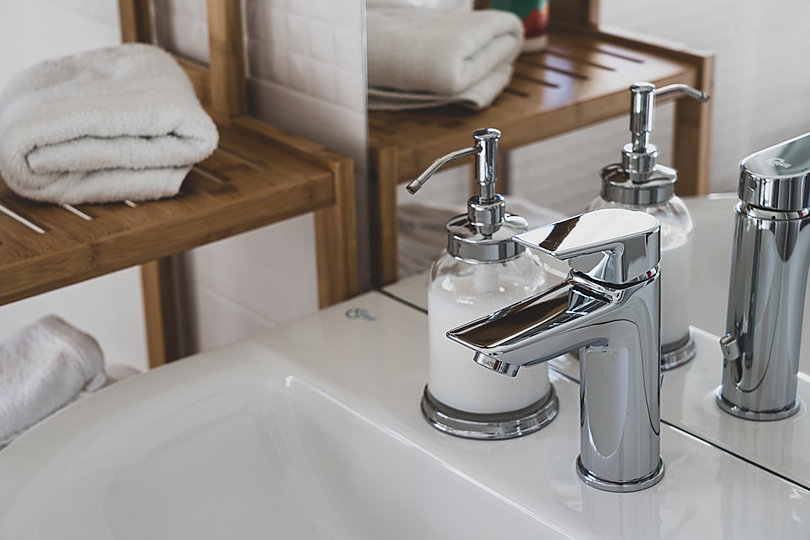 stainless-steel-faucet-on-white-ceramic-