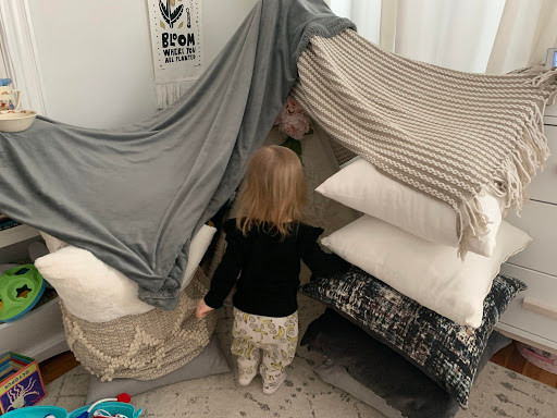 Reading in bed under pillow fort