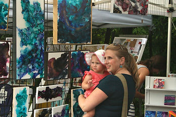 A mother holding hr daughter in front of an artists booth