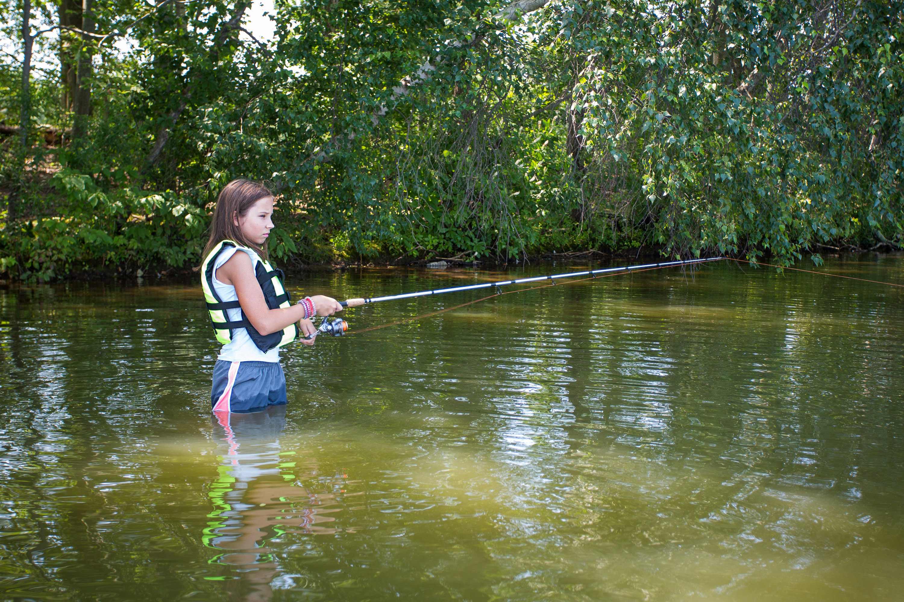 Young teenage girl fishing in the water