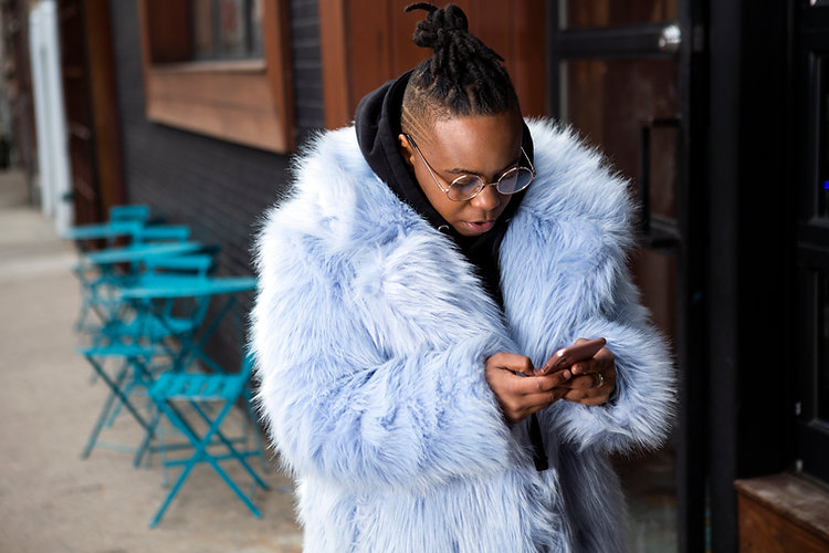 A transmasculine person with a furry blue coat checking their phone.