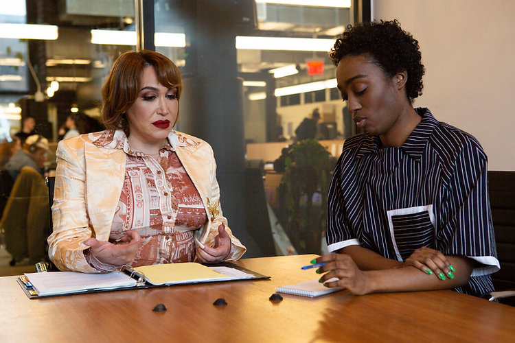 A transfeminine executive meeting with a young genderfluid professional