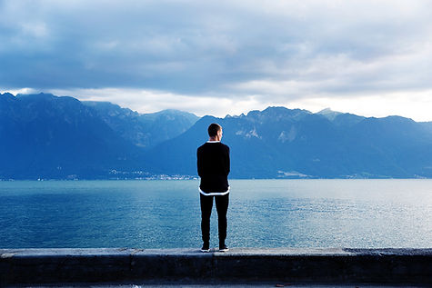 The back of a man looking at a lake with mountains on the other side