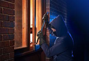 Burglar Using Crowbar To Break Into a Ho