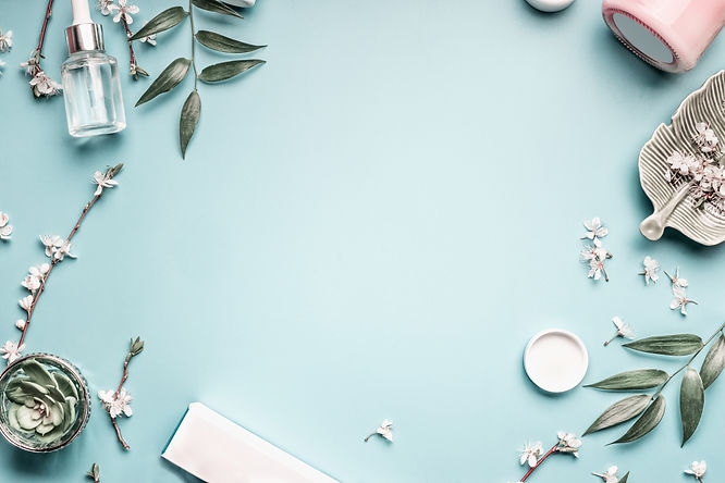 Beauty background with facial cosmetic products, leaves and cherry blossom on pastel blue