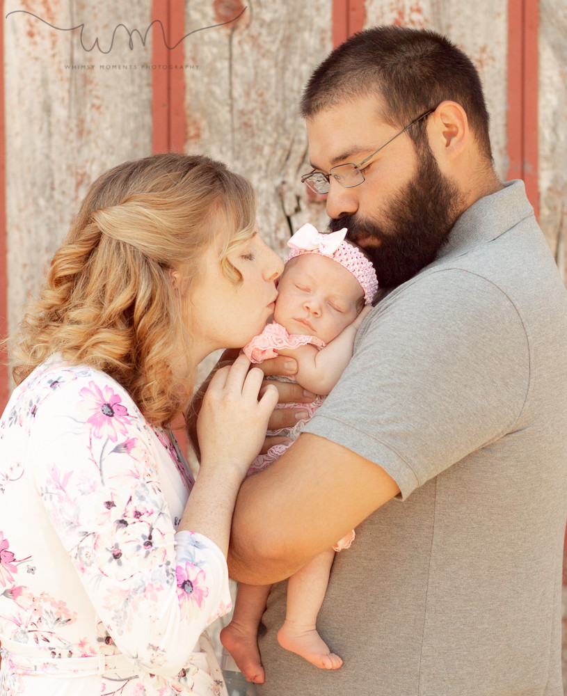 Newborn Session in Akron, Colorado baby girl Mama and Daddy kissing her head by Whimsy Moments Photography
