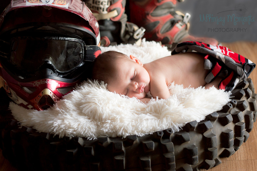 Newborn in Dirt bike tire with helmet and boots