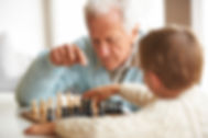 elderly-man-teaches-grandson-about-chess
