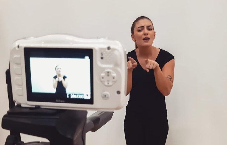 Foto de interprete de libras sendo filmada fazendo sinais em libras
