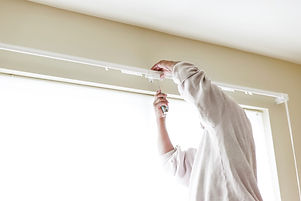 House painter reinstalls a drapery rod RM