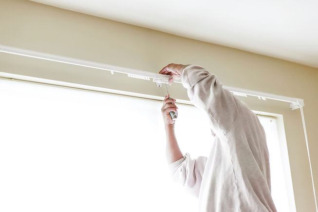 House painter reinstalls a drapery rod R