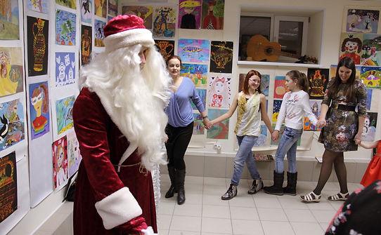 Дед Мороз, дети в хороводе, детские рисунки на стенах, встреча Нового года в художественной студии