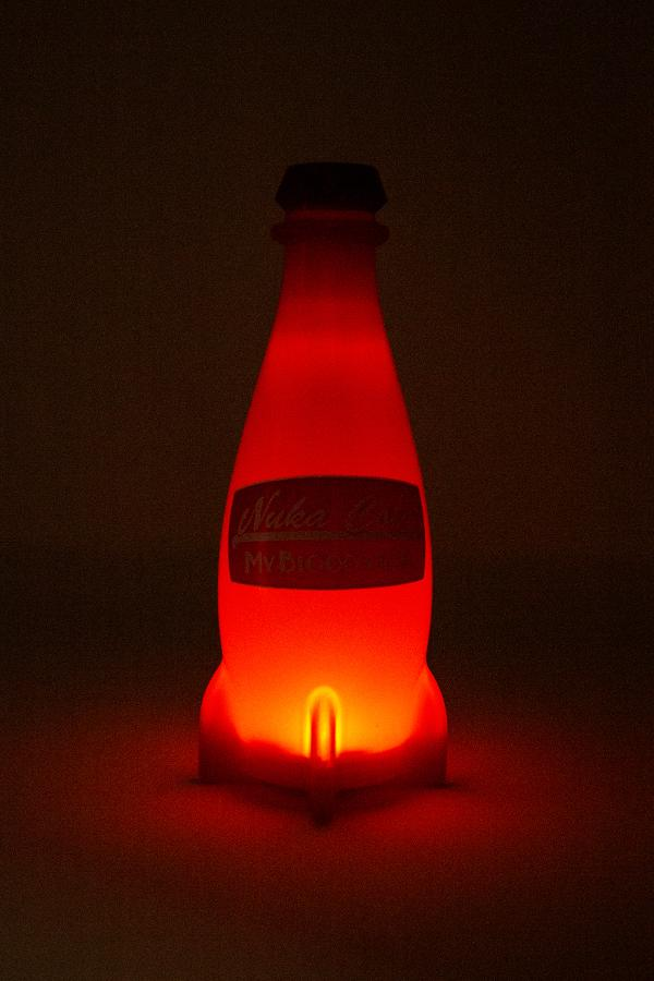 red Nuka-Cola bottle shaped LED lamp from Fallout with the bottle light turned on so it's glowing red in the dark