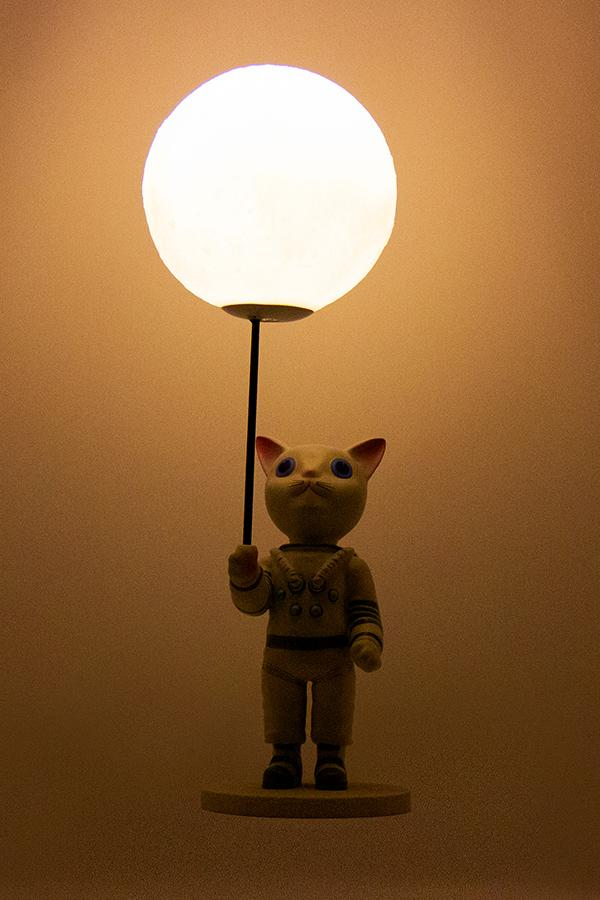 Mr. Pebbles (a white cat with blue eyes wearing a white space suit) from Fallout 76 desk lamp with the light turned on, front profile
