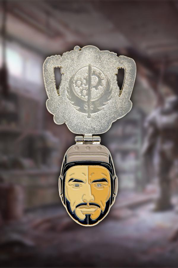 The T-60 power armor helmet from Fallout 4 soft enamel pin showing it opened up, with a brotherhood of steel logo on the underside of the pin and Paladin Danse's face on the bottom