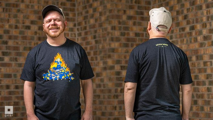 A man wearing a t-shirt with one Vault Boy from Fallout standing on top of a pile of dead Vault Boys