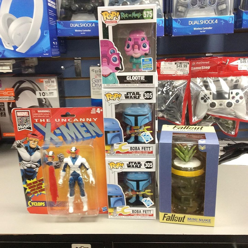 Four pop culture figures and a mini nuke from Fallout planter on display at a gaming store, with gaming peripherals in the background