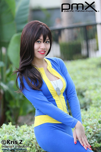 Vault Dweller from Fallout 1 cosplay, the iconic blue and yellow jumpsuit with green shrubs and plants in the background