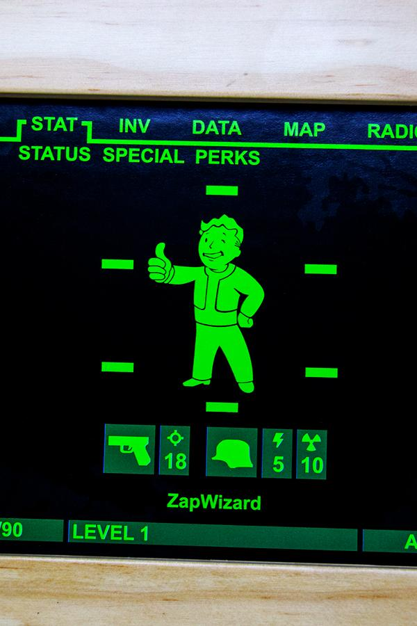 a close up of the Vault Boy screen giving a thumbs up on the Pip-Boy 3000 Mark IV model from Fallout 4 wooden art