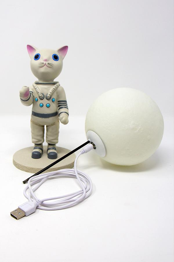 Mr. Pebbles (a white cat with blue eyes wearing a white space suit) from Fallout 76 desk lamp, showing detail of the moon shaped lamp