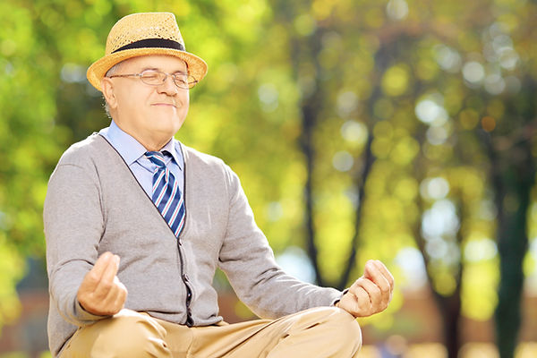 Senior gentleman meditating seated on a
