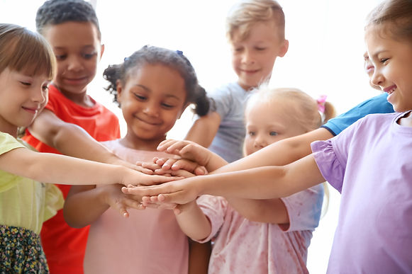 Children in a circle showing that they are a team.