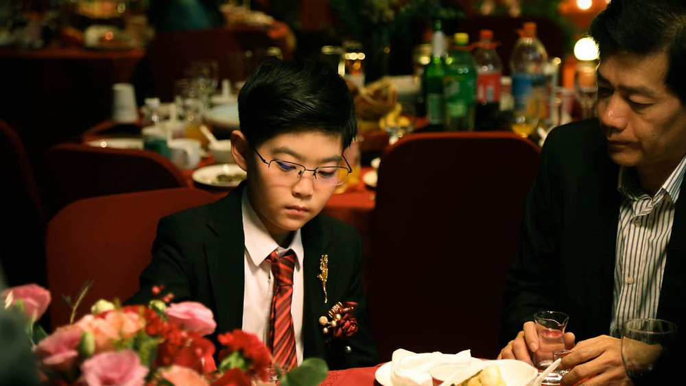 Two people, a boy and a man, are sitting at a dinner table during a wedding.