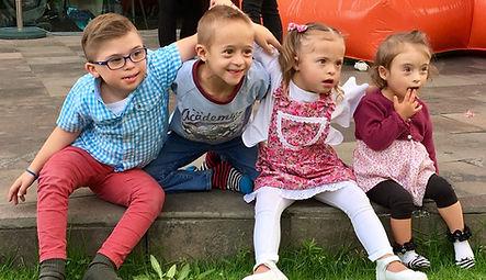 En la foto se encuentran 4 niños abrazados, tres de ellos con Síndrome de Down