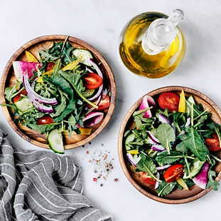 2 wooden bowls of healthy salads and oil served at a yoga retreat