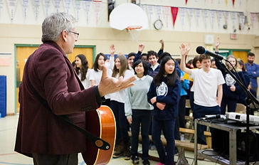Charlie Angus with guitar and signing with high school students