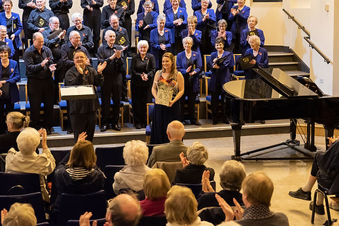 Choir and Musical Director applauding the soprano soloist