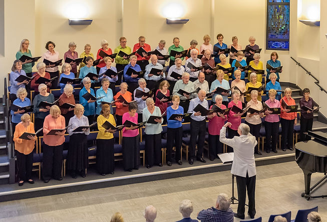 Summer concert of lighter music with the choir wearing a rainbow variety of brightly coloured shirts