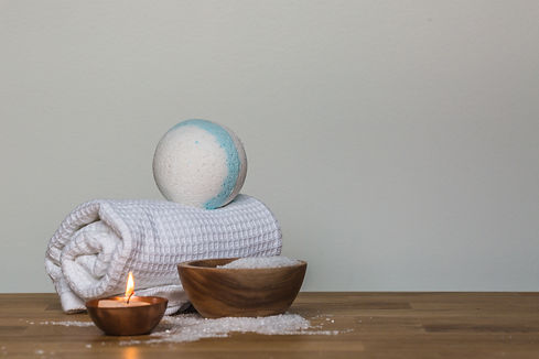 photo-of-towel-and-bath-bomb-near-candle