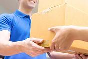 Delivery man in blue uniform handing par