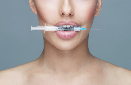 Doctor injecting in a beautiful face of