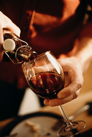 person-pouring-wine-on-wine-glass-317115