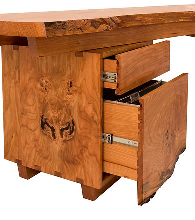 A fallen cherry tree in the back yard is transformed into a corner desk.  To celebrate the birth of a child, impressions of the baby's hand and foot are embedded into the desktop.