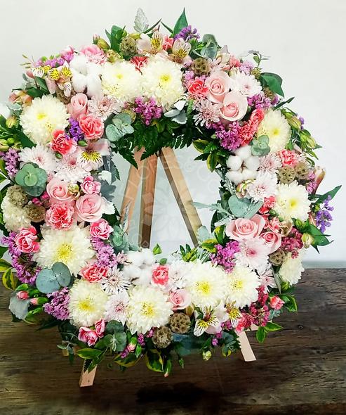 Corona variedad de flores en tonos rosas y morados