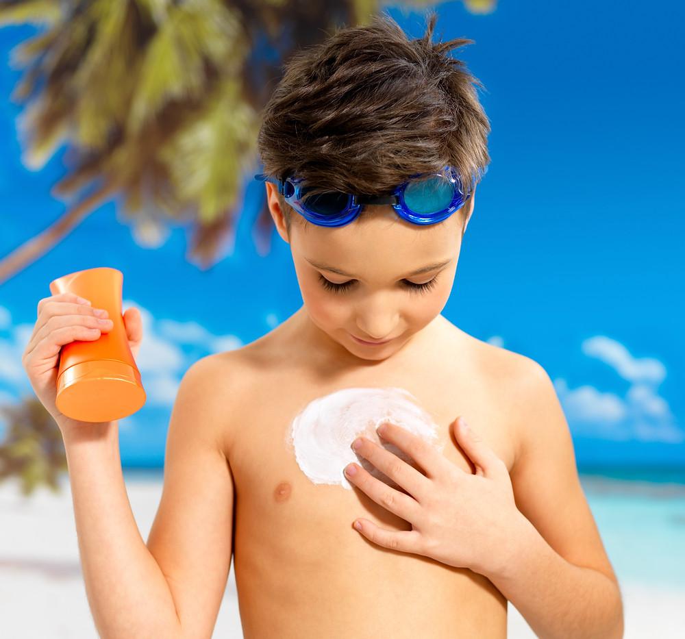 Criança aplicando o protetor solar