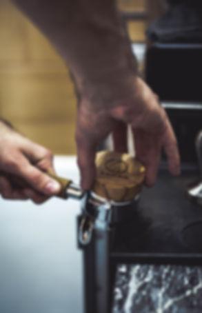 Baista distributing coffee grounds in the portafilter, photo taken in Bloom Coffee Belgrde.
